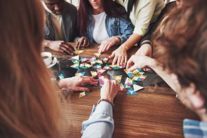 Image of friends playing a board game | Featured image for How to Teach Board Games blog.